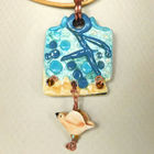 Pendant_necklace__gold_leather_cord__aqua_porcelain_rectangle__yellow_bird_dangle_001